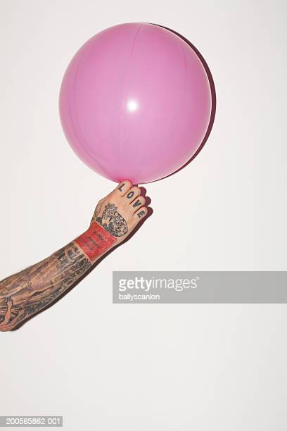 Tattooed hand holding pink balloon, against white background