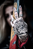 Close up of a tattooed hand with model in background