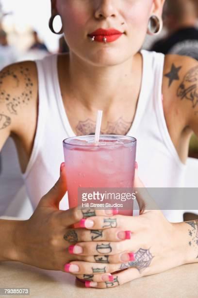 Tattooed Hispanic woman holding drink