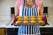 Tattooed Hispanic woman holding tray of muffins