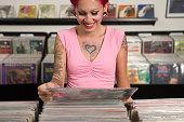 Tattooed Hispanic woman looking at record albums