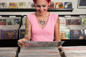 Tattooed Hispanic woman looking at record albums