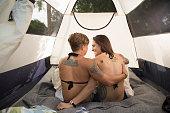 Tattooed lesbian couple sitting in tent.