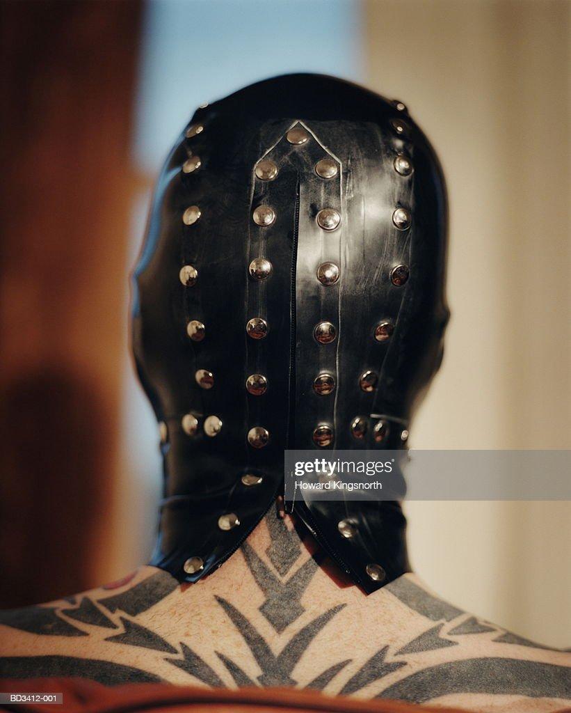 Tattooed man wearing rubber fetish mask, rear view