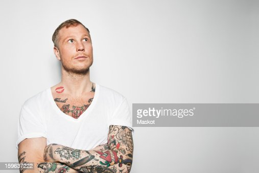 Tattooed man with arms crossed looking away against grey background