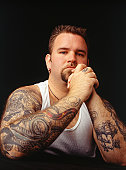 Tattooed man with hands together, portrait