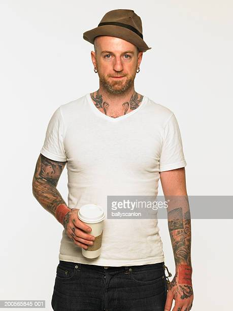 Tattooed man with hat and coffee cup, against white background, portrait
