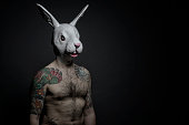 Isolated tattooed man with rabbit mask