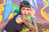 tattooed rebel girl posing against a wall painted with colorful graffiti