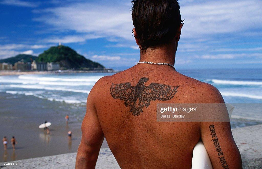 Tattooed surfer looking at beach, San Sebastian, Spain : Stock Photo