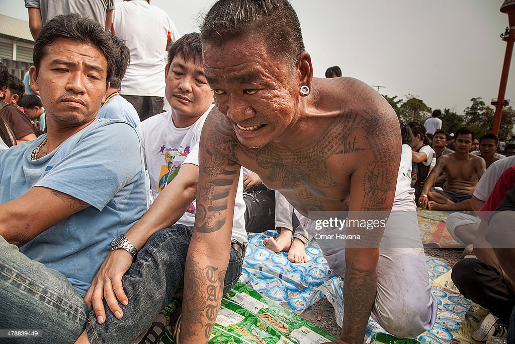 A tattooed Thai devotee reportedly possessed by spirits crawls as he tries to pay his respect to a statue of Lord Buddha during the celebration of...
