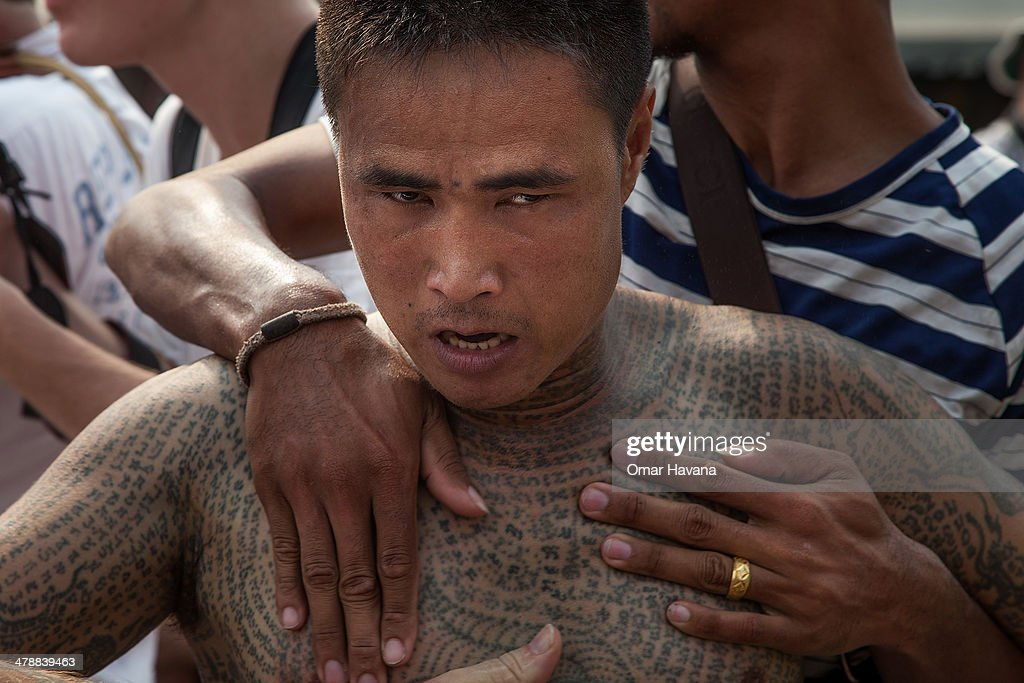 A tattooed Thai devotee reportedly possessed by spirits is helped by volunteers during the celebration of the annual Tattoo festival at Wat Bang Phra...