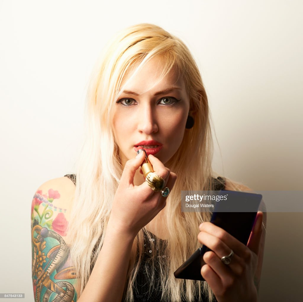 Tattooed woman applying lipstick.