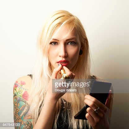 Tattooed woman applying lipstick.