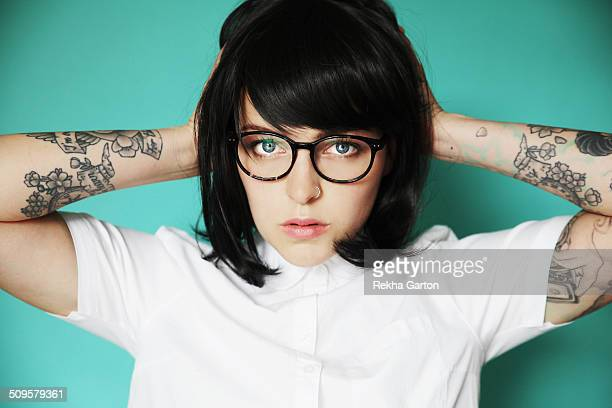 Tattooed woman in a white shirt holding head