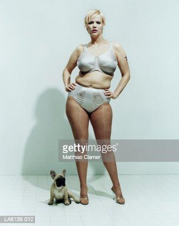 Tattooed woman in underwear standing beside dog, portrait