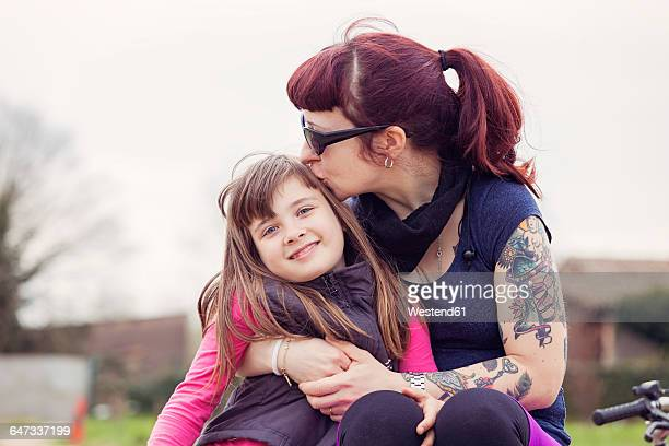 Tattooed woman kissing her smiling little daughter