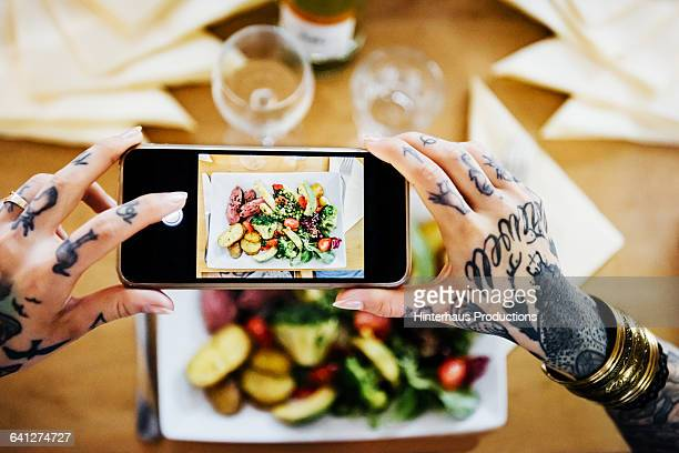 Tattooed woman taking pictures of their Food