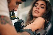 Tattoo artist creating a tattoo on a girl's arm. Focus on tattoo machine
