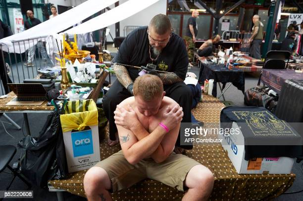 A tattooist inks a customer at The London International Tattoo Convention in Tobacco Dock east London on September 23 2017 / AFP PHOTO / NIKLAS...