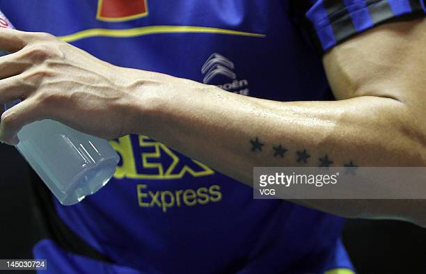 Tattoos are seen on the forearm of Lin Dan as he competes against Simon Santoso of Indonesia in their Group A match during the Thomas Cup world...