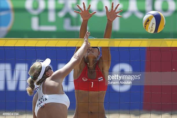Tatyana Mashkova of Kazakhstan shoots past Yupa Phokongploy of Thailand during the Women's Beach Volleyball Preliminary Round 2014 Asian Games match...