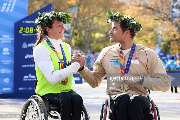 Tatyana McFadden of the United States and Marcel Hug of Switzerland shake hands while wearing their medals after finishing first in Women's and Men's...