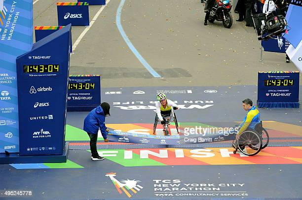 Tatyana McFadden of the United States crosses the finish line to win the Women's Professional Wheelchair Division at TAG Heuer Official Timekeeper...