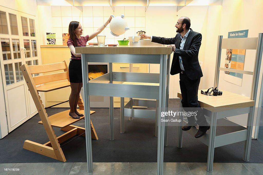 Tatyana Sukhareva and Fadi Zatari, both interns at the Bundestag, pretend to take coffee while exploring the 'How Children see The Wold' exhibit in Paul-Loebe-Haus at the Bundestag on April 25, 2013 in Berlin, Germany. The exhibit, which features an over-scaled kitchen complete with a breakfast table, chairs, a kitchen counter, oven and frying pan, marks the 25th anniversary of the Bundestag's Children's Commission and highlights the challenges and the dangers children face in everyday life.
