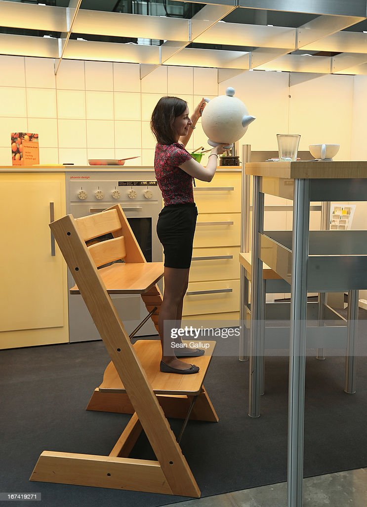 Tatyana Sukhareva, and intern at the Bundestag, stands on a child's bigger-than-life highchair as she pretends to take coffee while exploring the 'How Children see The Wold' exhibit in Paul-Loebe-Haus at the Bundestag on April 25, 2013 in Berlin, Germany. The exhibit, which features an over-scaled kitchen complete with a breakfast table, chairs, a kitchen counter, oven and frying pan, marks the 25th anniversary of the Bundestag's Children's Commission and highlights the challenges and the dangers children face in everyday life.