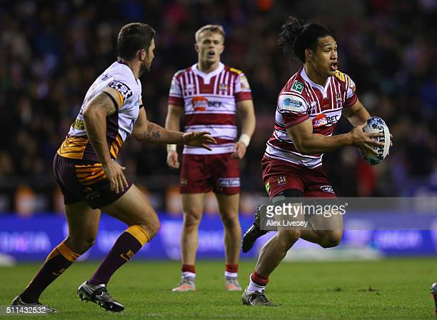 Taulima Tautai of Wigan Warriors is carries the ball past Matt Gillett of Brisbane Broncos during the World Club Series match between Wigan Warriors...