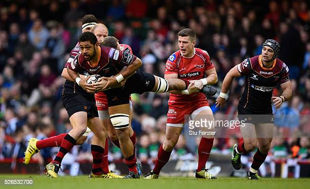 Taulupe Faletau is tackled by Scott Williams of the Scarlets during the Guinness Pro 12 match between Newport Gwent Dragons and Scarlets at...
