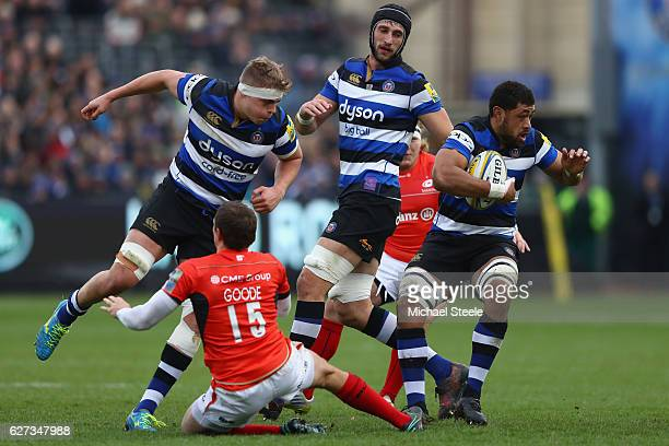 Taulupe Faletau of Bath avoids the challenge from Alex Goode of Saracens as Tom Ellis lends support during the Aviva Premiership match between Bath...