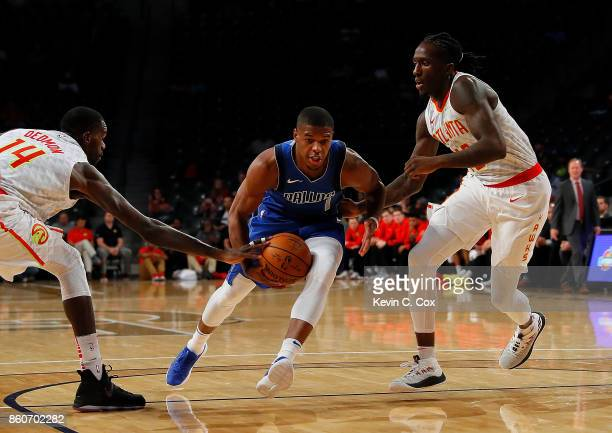 Taurean Prince defends as Dewayne Dedmon of the Atlanta Hawks reaches for a steal against Dennis Smith Jr #1 of the Dallas Mavericks at McCamish...