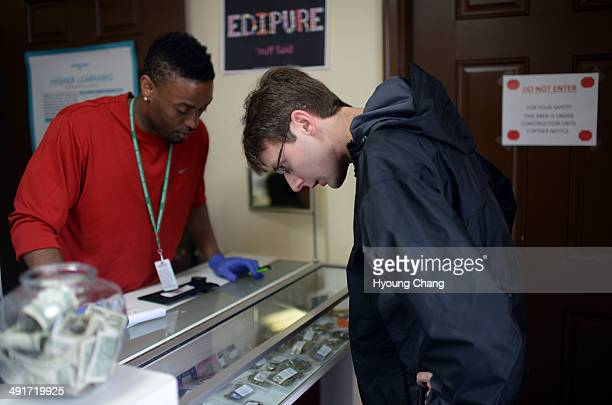 Taurean Wilson of Botana Care left helps Kevin Murphy of Arvada purchasing recreational marijuana Northglenn Colorado May 16 2014