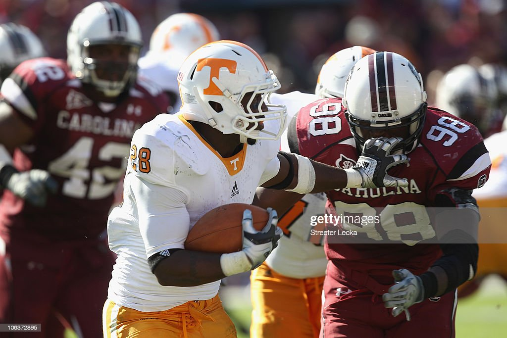 Tauren Poole #28 of the Tennessee Volunteers grabs the facemask of Devin Taylor #98 of the South Carolina Gamecocks during their game at Williams-Brice Stadium on October 30, 2010 in Columbia, South Carolina.