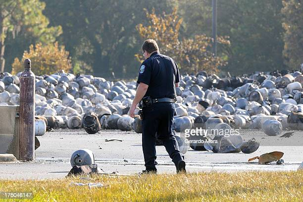 Tavares police officer walks past propane cylinders on the grounds of a propane gas company after a series of explosions rocked the central Florida...