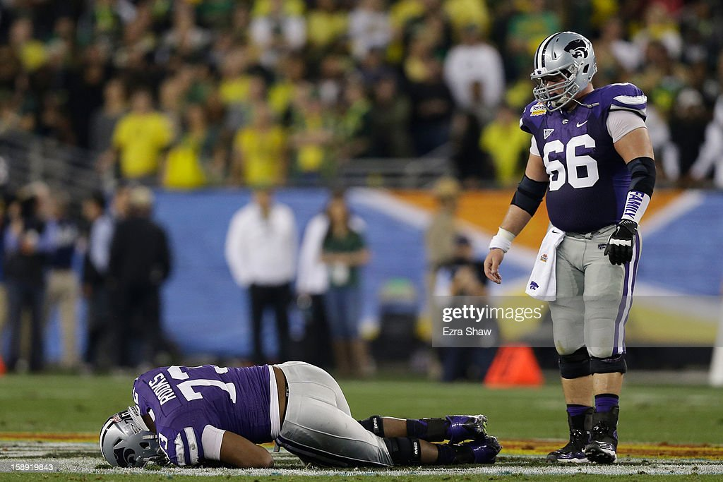 Tavon Rooks #73 lays on the field injured as BJ Finney #66 of the Kansas State Wildcats looks on during the Tostitos Fiesta Bowl against the Oregon Ducks at University of Phoenix Stadium on January 3, 2013 in Glendale, Arizona.