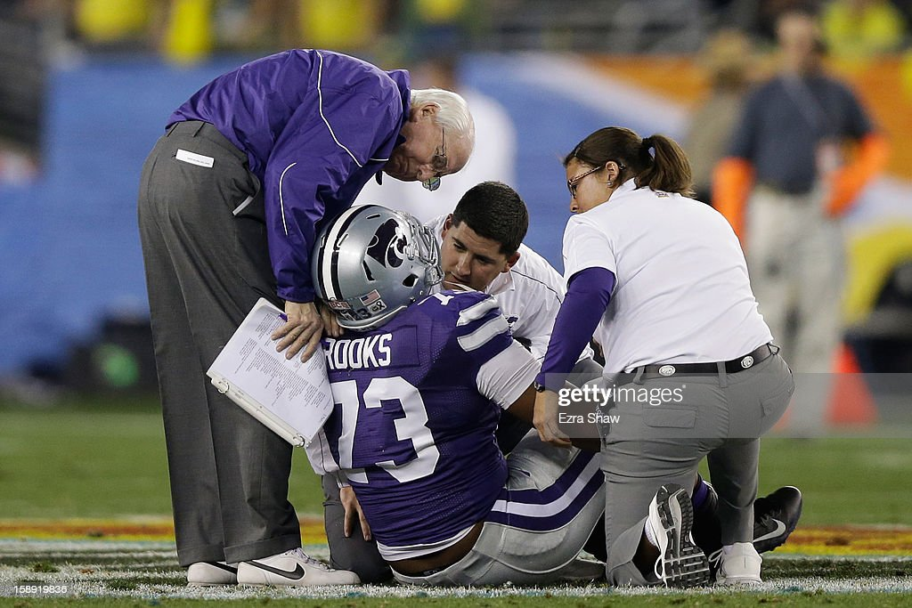 Tavon Rooks #73 of the Kansas State Wildcats receives attention after being injured on a play against the Oregon Ducks during the Tostitos Fiesta Bowl at University of Phoenix Stadium on January 3, 2013 in Glendale, Arizona.