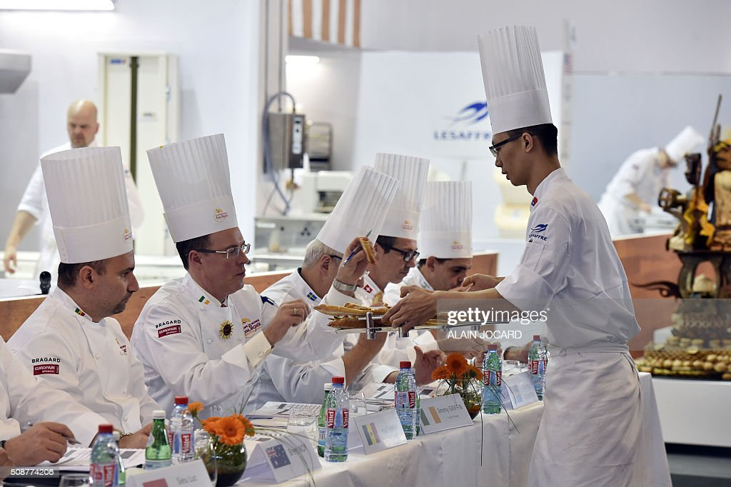 A Tawain's team member shows his work to the jury during the Bakery world cup, as part of the Europain fair, on February, 6, 2016, in Villepinte near Paris. / AFP / ALAIN JOCARD