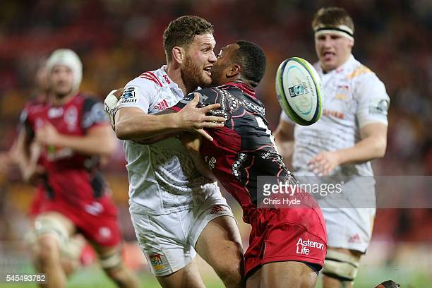Tawera Kerr Brown of the Chiefs passes while tackled by Samu Kerevi of the Reds during the round 16 Super Rugby match between the Reds and the Chiefs...