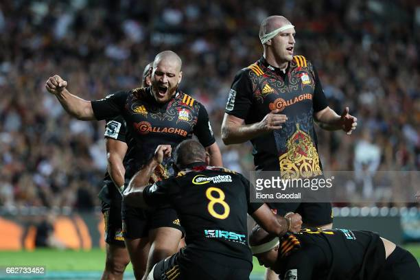 Tawera KerrBarlow celebrates a try with Brodie Retallick and Michael Leitch during the round six Super Rugby match between the Chiefs and the Bulls...