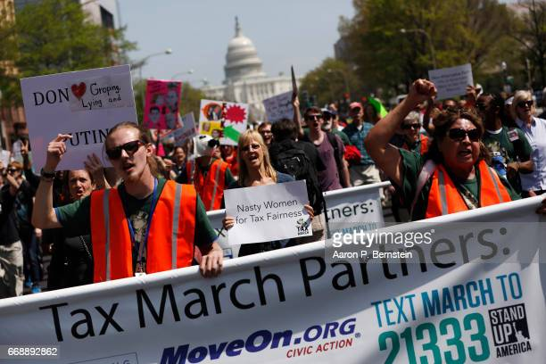 Tax Day demonstrators march away from the US Capitol April 15 2017 in Washington DC Activists gathered in cities nationwide to demand President...