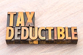 tax deductible word abstract in vintage lettepress wood type, finance concept