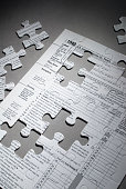 US tax form 1040 with jigsaw puzzle pieces cut out