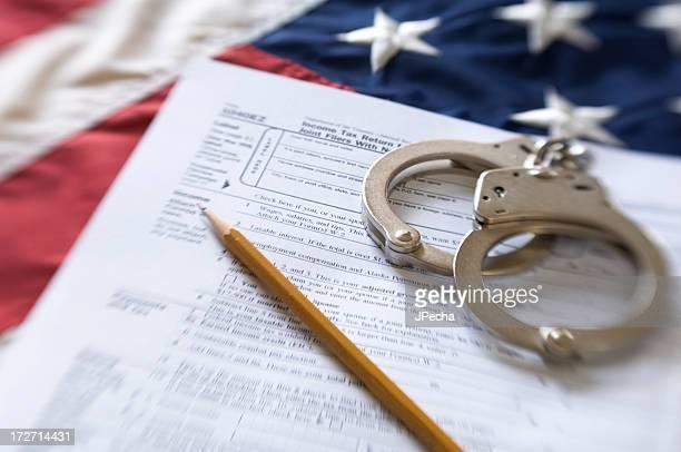 US-amerikanisches Steuerformular und Hancuffs über amerikanische Flagge Geringe Tiefenschärfe
