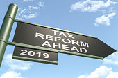Green and black colored traffic sign with tax reform ahead text. in the blue colored sky background composition. The concept of tax reform time traffic sign recalls people that it is time to tax refor