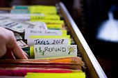 Tax refund conceptual tax season tax preparation photography with files and tax forms in filing cabinet and words refund and taxes 2018 written on file folders  with light bulb for ideas and US dollar
