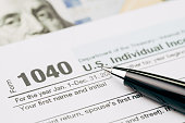 Tax time concept, selective focus on pen on 1040 US individual income tax filling form with US dollar bill, calculate from yearly revenue to pay the government.