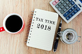 Tax Time text on notepad - coffee, jar coins, pen and calculator on top of wooden table.